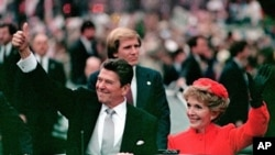 President Ronald Reagan gives a thumbs up to the crowd while his wife, first lady Nancy Reagan, waves from a limousine during the inaugural parade in Washington following Reagan's swearing in as the 40th president of the United States, (File).