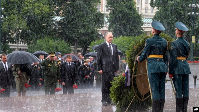 Tổng thống Nga Vladimir Putin đứng nghiêm dưới trời mưa to trong dịp tới viếng mộ chiến sĩ vô danh ở thủ đô Moscow hồi tháng Sáu.