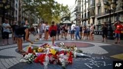 巴塞羅那歷史悠久的蘭布拉大道(Las Ramblas)上,一名女子在紀念儀式周圍放了一朵花,悼念2017年恐怖襲擊的遇難者。(2018年8月16日)