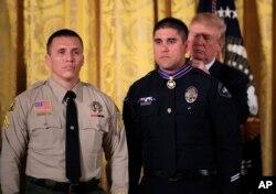 El presidente Donald Trump coloca la Medalla al Valor al oficial de policía Nicholas Koahou, de Redlands, California, durante una ceremonia en el Salón Oriental de la Casa Blanca, a la izquierda el Cabo Rafael Ixco del Departamento del Alguacil del Condado de San Bernardino, California, que también recibió el honor. Martes 20 de febrero de 2018.