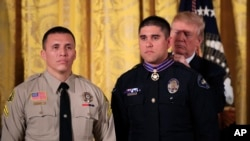President Donald Trump awards the public safety Medal of Valor to Officer Nicholas Koahou of Redlands (Calif.) Police Department during a ceremony in the East Room of the White House, Feb. 20, 2018. Standing on the left is fellow awardee Corporal Rafael Ixco of San Bernardino County Sheriff's Department, Calif.
