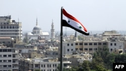 The Syrian flag flutters above Damascus, September 20, 2012.