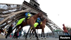 Mounted French Republican Guards patrol under the Eiffel Tower as the French capital remains under a high security alert following recent fatal shootings and ahead of the World Climate Conference 2015, in Paris, France, Nov. 28, 2015.