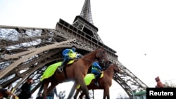 FILE - Mounted French Republican Guards patrol under the Eiffel Tower in Paris, France, Nov. 28, 2015.