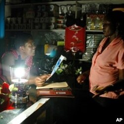 Ugandan women chat in a shop lit by a paraffin lamp in the capital Kampala (file photo)