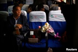 A man sits next to a bag containing the ashes of a deceased relative as he travels on a ferry before a sea burial ceremony in Shanghai, May 10, 2014.