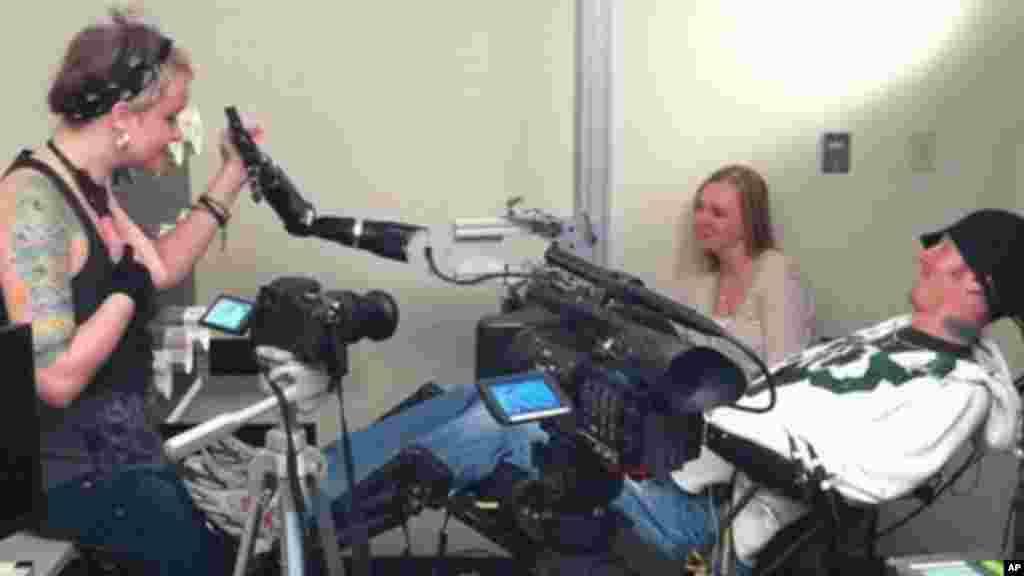 La vidéo fournie par le Centre Médical Center de l'Université de Pittsburgh, prise lundi 19 septembre 2011, montre un sujet tétraplégique,Tim Hemmes, utilisant une prothèse de bras mécanique, avec Katie Schaffer, pendant une des séances d'essais. (AP Photo / UPMC)