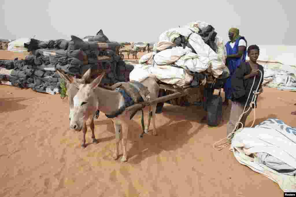 Des agents du HCR acheminant par charette des tentes au camp de Mbera, à 40 km de la frontière malienne.