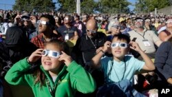 A crowd wears protective glasses as they watch the beginning of the solar eclipse from Salem, Oregon, Aug. 21, 2017.