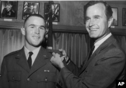 George W. Bush, left, is shown with his father, George H.W. Bush, in this photo from 1968.