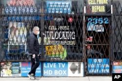 Seoran pria berjalan di depan sebuah toko yang tutup di tengah pandemi COVID-19 di Chicago, 30 April 2020. (Foto: dok).