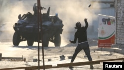 A protester throws a glass bottle containing paint at a riot police armoured personnel carrier during anti-government clashes in the village of Sitra, south of Manama, Bahrain, Feb. 14, 2016.