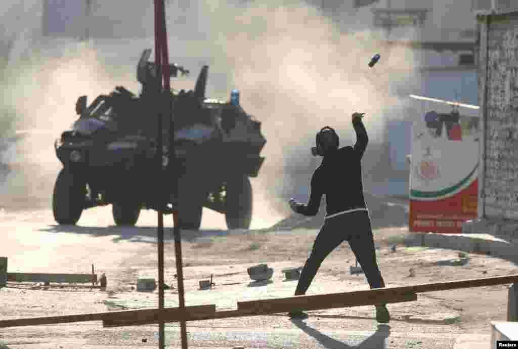 بحرین میں مظاہرے کے دوران ایک مشتعل نوجوان پینٹ کی بوتل پولیس کی گاڑی پر پھینک رہا ہے۔