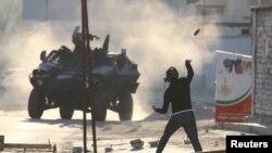 Seorang demonstran melemparkan botol kaca berisi cat ke arah kendaraan lapis baja polisi anti huru-hara saat bentrokan di Sitra, Manama selatan, 14 Februari 2016.