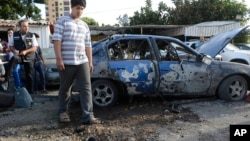 Một người dân Li-băng nhìn một mãnh của tên lửa, rơi trúng địa điểm trưng bày xe ở Beirut, 26/5/13