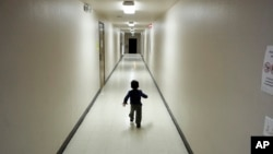 FILE - An asylum-seeking boy from Central America runs down a hallway after arriving from an immigration detention center to a shelter in San Diego, Dec. 11, 2018.