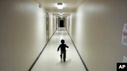 资料照片:一名寻求庇护的中美洲男孩从一处移民羁押中心转到加州圣迭戈的一处庇护所后,跑在走道里。(2018年12月11日)