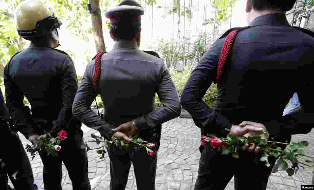 Thai police officers hold roses given by pro-army supporters behind their back as they stand guard outside the Australian embassy in Bangkok, June 4, 2014.