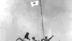 Japanese soldiers raise their flag over the central government building in Nanking after seizing the city in 1937