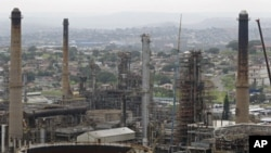 FILE - Chimneys from the Engen oil company are seen on the outskirts of the city of Durban, South Africa, Nov. 30, 2011.