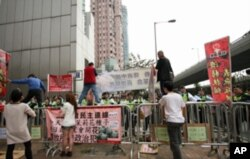 示威者星期天早上准备将茉莉花种在中联办大楼前的花园内,被香港警察用铁栅栏阻挡