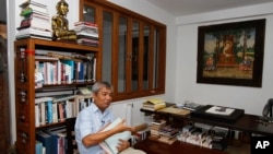 In this July 2, 2014 photo, Director of Documentation Center of Cambodia Youk Chhang holds Poch Younly's dairy book during an interview with the Associated Press, in Phnom Penh.