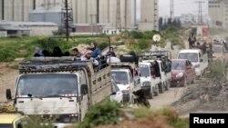 Warga yang takut dengan serangan udara dari pasukan pemerintah Suriah melarikan diri dari Idlib, setelah pasukan pemberontak mengambil alih kota itu (28/3). (Reuters/Khalil Ashawi)