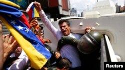 El líder opositor Leopoldo López es llevado a bordo de un vehículo de la Guardia Nacional luego de entregarse a las autoridades.