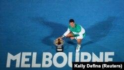 Le Serbe Novak Djokovic fête avec le trophée après avoir remporté la finale contre le Russe Daniil Medvedev à Melbourne, Australie, le 21 février 2021