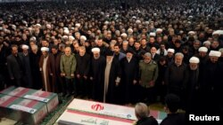 Description: Iran's Supreme Leader Ayatollah Ali Khamenei and President Hassan Rouhani pray near the coffins of Iranian Major-General Qassem Soleimani, head of the elite Quds Force, and Iraqi militia commander Abu Mahdi al-Muhandis, who were killed in an american air strike