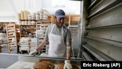 Nothing beats warm bread and butter! In this photo, baker Chad Robertson checks loaves of bread coming out of an oven at the Tartine Manufactory in San Francisco, California, 2017. (AP Photo/Eric Risberg)