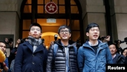 Pro-democracy activists (L-R) Joshua Wong, Alex Chow and Nathan Law pose outside the Court of Final Appeal before a verdict on their appeal in Hong Kong, Feb. 6, 2018.