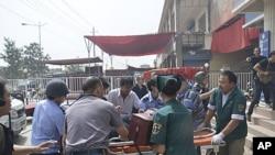图为7月18日新疆和田发生冲突之后,人们从警察局抬出担架。