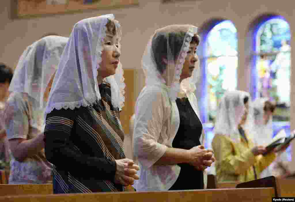 People pray for victims of the 1945 atomic bombing during a mass at the Urakami Cathedral in Nagasaki on the 68th anniversary of the bombing of the city, August 9, 2013. (Reuters/Kyodo)