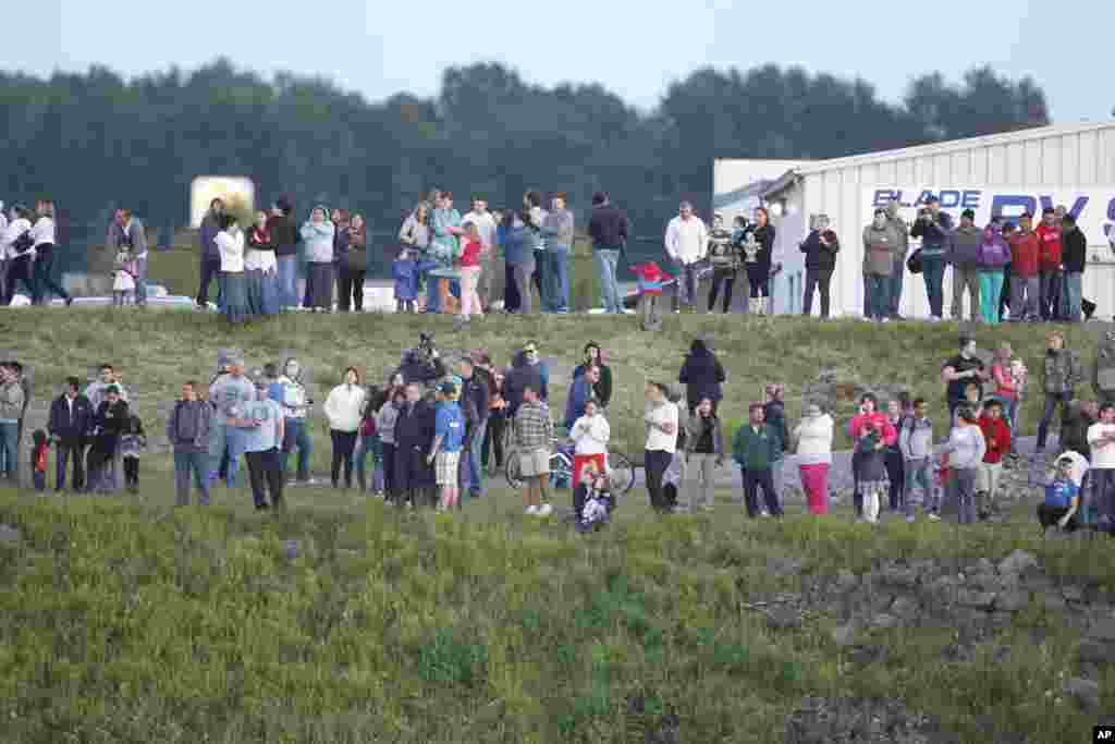 People stand on the south bank of the Skagit River to watch the rescue operation following Interstate 5 bridge collapse, Mount Vernon, Washington, May 23, 2013.