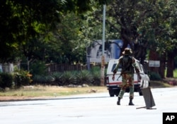 An armed soldier turns away a vehicle during lockdown in Harare, Zimbabwe, April 13, 2020, in an effort to curb the spread of the coronavirus.