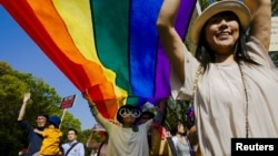 FILE - Participants hold a rainbow flag during the Tokyo Rainbow Pride parade in Tokyo, April 26, 2015. A human rights group said May 5 that Japan has failed to protect its lesbian, gay, bisexual and transgender (LGBT) students.