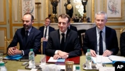 France's President Emmanuel Macron, center, France's Prime Minister Edouard Philippe, left, and France's Finance Minister Bruno Le Maire, right, attend a meeting with the representatives of the banking sector at the Elysee Palace, in Paris, Dec.11, 2018.