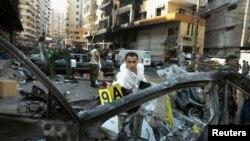 Seorang ahli forensik memeriksa sebuah kendaraan di lokasi ledakan bom di pinggir kota Beirut (16/8). Ledakan bom mobil di wilayah Rweiss, basis kelompok militan Syiah Hizbullah di Lebanon hari Kamis (15/8) ini dilaporkan telah menewaskan sedikitnya 22 orang.