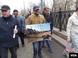 FILE – A protester holds a photo during a mass demonstration in Moscow against the Russian annexation of Crimea in 2014.