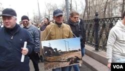 今年3月莫斯科反对俄罗斯吞并克里米亚的大规模群众游行中,示威者手举车臣战争照片,警告俄罗斯在走车臣战争之路。(美国之音白桦 拍摄)