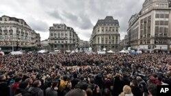 Les gens observent une minute de silence à la Place de la Bourse dans le centre de Bruxelles, le 23 Mars , ici 2016. (AP Photo/Martin Meissner)