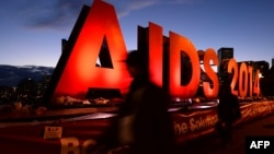 "People walk past an ""AIDS 2014"" sign promoting the 20th International AIDS Conference in Melbourne on the eve of the concluding session of the conference, July 24, 2014."