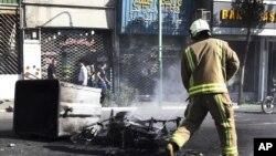 Lính cứu hỏa Iran bên cạnh một chiếc xe máy bị đốt cháy trên đường phố ở trung tâm Tehran, ngày 3/10/2012