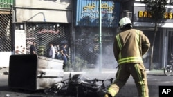 In this photo taken by an individual not employed by the Associated Press and obtained by the AP outside Iran, an Iranian fire fighter extinguishes a burned motorcycle in a street in central Tehran, near Tehran's old main bazaar, October 3, 2012.