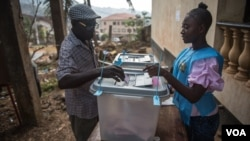 A voter casts his ballot at a polling station in Freetown, Sierra Leone, March 7, 2018. (Photo: Jason Patinkin / VOA)