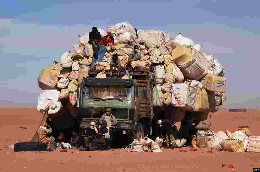 People sit on a overloaded truck in Madama, Niger, near the border with Lybia.