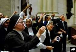 Nuns, some angered by the pushing and shoving, scramble to get into position for a photograph of the Pope as he leaves St. Patrick's Cathedral, Sept. 24, 2015 in New York.