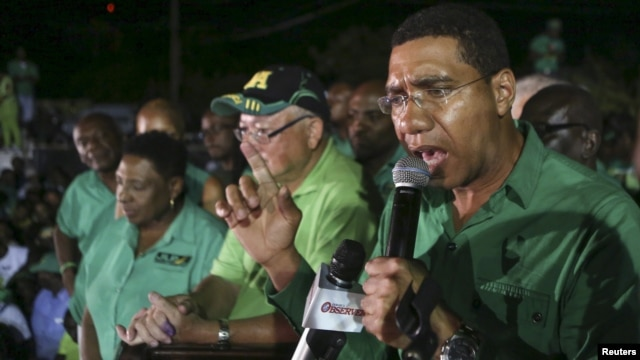 FILE - Andrew Holness (R), leader of the opposition Jamaican Labour Party, speaks to supporters at the party headquarters in Kingston, Jamaica, Feb. 25, 2016.