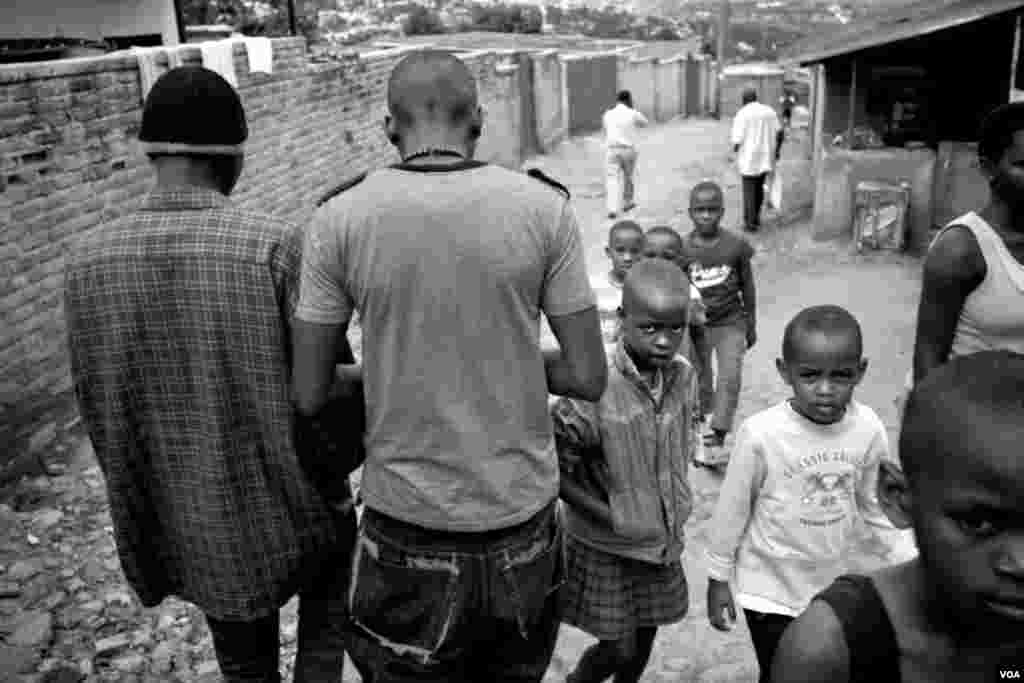Nshizirungu Amos (left) and Vansing walk among young children in the streets. The Rwanda genocide left orphans who still struggle with a lack of opportunities, terminal diseases, loneliness and distrust, which now threatens the new generation, Giporoso, Kigali, Nov. 27, 2013.